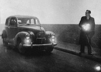 0526533 © Granger - Historical Picture ArchiveGREAT SMOG, 1952.  A man with a flashlight guiding a car through the street during the Great Smog of '52 in London. Photograph, December 1952.