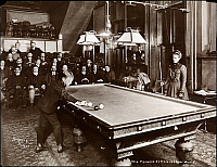 0163621 © Granger - Historical Picture ArchiveBILLIARDS, 1900.  Mrs. Frances Hoppe playing billiards with her son William F. Hoppe in a billiard room with seated spectators watching, 1900.