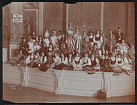 0166148 © Granger - Historical Picture ArchiveTAMMANY HALL DRESS BALL.   Group of primarily women in national dress, two as Uncle Sam and Liberty, assembled on a stage at Tammany Hall on 14th Street holding American flags with stage decorations visible, New York City. Photograph, 1906.