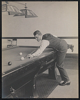 0166173 © Granger - Historical Picture ArchiveNEW YORK: BILLIARDS.   Billiards player William F. Hoppe standing at a pool table, with his leg up on the table, preparing to hit a ball with his cue. New York City, photograph, c1909.