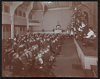 0166269 © Granger - Historical Picture ArchiveDEWITT MEMORIAL CHURCH.   Group of young men and some adults seated in the Dewitt Memorial Church at 280 Rivington Street watching some sort of a reading or performance with a Christmas tree on stage, New York City. Photograph, c1905.