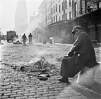 0172131 © Granger - Historical Picture ArchiveWATERFRONT, 1937.   Homeless man next to a dying fire in New York City. Photographed by David Robbins for the Federal Arts Project, a New Deal program, in 1937.