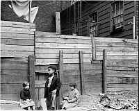 0172260 © Granger - Historical Picture ArchiveTENEMENTS AND CHILDREN.   Three children standing in front of a wooden fence; wooden tenements in the backgound. New York City, 1935.