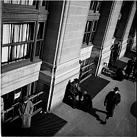 0172415 © Granger - Historical Picture ArchiveSOUTH FERRY BUILDING, 1940.   High angle view of a man shining the shoes of another man and pedestrians walking by the South Ferry Building at 1 State Street, New York City. Photograph, 1940.