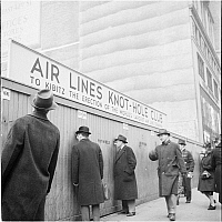 0172416 © Granger - Historical Picture ArchiveAIR LINES KNOT-HOLE CLUB.   Men peering through holes in a wooden fence. Sign reads: 'Air Lines Knot-Hole Club, To Kibitz the Erection of the World's Largest Air Line Terminal.' New York City, photograph, 1940.
