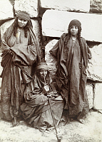 0246935 © Granger - Historical Picture ArchiveARABIA.   Bedouin women lean against a stone wall, one smokes a long foot pipe. Archibald Forder.