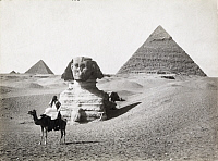 0248208 © Granger - Historical Picture ArchiveGIZEH, EGYPT.   A man rides a camel in front of the Great Sphinx and pyramids of Giza. J. P. Altberger.