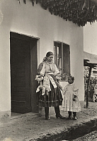 0248904 © Granger - Historical Picture ArchivePOSTYEN, HUNGARY.   A mother and child stand under corn drying over their home entrance. A. W. Cutler.