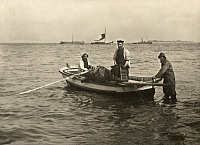 0249731 © Granger - Historical Picture ArchiveHELIGOLAND ISLAND, GERMANY.   Three fisherman hold nets and guide their boat out of shallow water. No Credit Given.