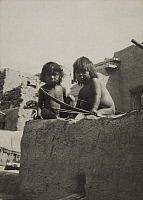 0251662 © Granger - Historical Picture ArchiveARIZONA, USA.   Two young Hopi children sit on a clay wall with a bow and arrow set. Frederick I. Monsen.
