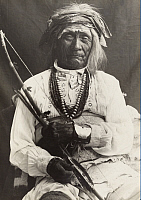 0251675 © Granger - Historical Picture ArchiveLAGUNA, NEW MEXICO, USA.   An old war chief, seated on a chair, poses with a bow and arrows. Frederick I. Monsen.
