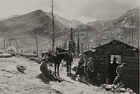0252548 © Granger - Historical Picture ArchiveBEAR LAKE REGION, ROCKY MOUNTAIN NATIONAL PARK, COLORADO, UNITED STATES.   A group of people sit around an outpost cabin at the end of a trail. Denver Tourist Bureau.