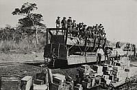 0253549 © Granger - Historical Picture ArchiveFUNGURUME, BELGIAN CONGO.   Men load a train with rubber tires with packages from their boat. Frank J. Magee.