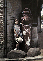 0254275 © Granger - Historical Picture ArchiveALFRISTON, SUSSEX, ENGLAND.   A young girl stands with a figurehead outside the Star Inn. Clifton R. Adams.