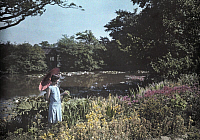 0254290 © Granger - Historical Picture ArchiveCROWHURST PLACE, SURREY, ENGLAND.   A woman admires the flower-bordered pond at Crowhurst Place. Clifton R. Adams.