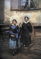 0254309 © Granger - Historical Picture ArchiveMEISTRATSHEIM, BAS-RHIN, ALSACE REGION, FRANCE.   Two women stand on stairs in great feast day attire. Gervais Courtellemont.