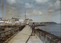 0254375 © Granger - Historical Picture ArchiveDOUARNENEZ, BRITTANY REGION, FRANCE.   Locals walk the pier in Douarnenez. Gervais Courtellemont.