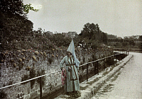 0254563 © Granger - Historical Picture ArchiveSENLIS, OISE, FRANCE.   A woman peers over a railing in a 15th-century dress. Gervais Courtellemont.