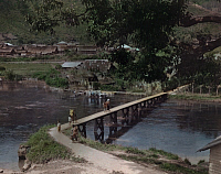 0255425 © Granger - Historical Picture ArchiveTAKINGUN, SUMATRA, INDONESIA.   People use one of the footbridges to cross the river in Takengon. Maynard Owen Williams.