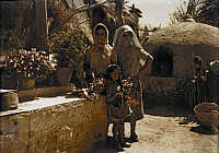 0255669 © Granger - Historical Picture ArchiveMURCIA, SPAIN.   Peasant girls collect flowers in their baskets in this courtyard. Gervais Courtellemont.