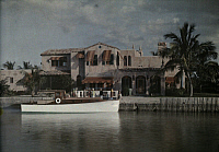 0255948 © Granger - Historical Picture ArchiveCOLLINS CANAL, MIAMI BEACH, FLORIDA, USA.   A boat docked beside a home located on Collins Canal. Clifton R. Adams.