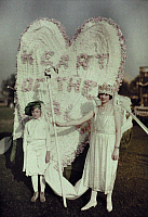 0256201 © Granger - Historical Picture ArchiveWINCHESTER, VIRGINIA, USA.   Two people pose with an Apple blossom festival float. Charles Martin.