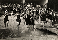 0256568 © Granger - Historical Picture ArchiveWOMEN.   A group of women in swimsuits race through a course of sand and water. No Credit Given.