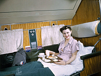 0256899 © Granger - Historical Picture ArchiveMEAL ON AIRPLANE.   A female passenger on an airplane enjoys a meal and a spacious seat. Luis Marden.
