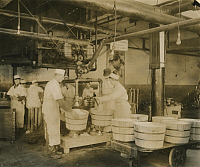 0257342 © Granger - Historical Picture ArchiveUNITED STATES.   Butchers use factory machines to fill tubs with pure lard. Us Dept Of Agriculture.