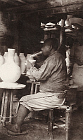 0257824 © Granger - Historical Picture ArchiveCHING-TEH-CHEN, CHINA.   A potter blows glaze onto a porcelain vase with a bamboo tube. Frank B. Lenz.