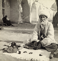0258504 © Granger - Historical Picture ArchiveKOKAND, UZBEKISTAN.   A blind fortune teller sits cross-legged on a rug dotted with pebbles. Maynard Owen Williams.