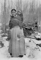 0108236 © Granger - Historical Picture ArchiveCANADA: INDIAN MOTHER.   A Dene woman carrying her child and a bundle of wood on her back in a forest in northwestern Canada. Photograph, 20th century.
