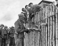 0108702 © Granger - Historical Picture ArchiveDACHAU LIBERATED, 1945.   An American soldier handing out cigarettes to inmates of the Nazi concentration camp at Dachau, near Munich, Germany, 29 April 1945, the day U.S. troops liberated the camp near the end of World War II.