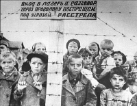 0108746 © Granger - Historical Picture ArchiveWWII: CHILD PRISONERS, 1944.   Russian children in a transit camp in Petrozadovsk, East Karelia, during World War II, with a sign on the fence threatening death to anyone who attempts to enter the camp or speak with the inmates. Photographed on 29 June 1944, one day after the withdrawal of the occupying Finnish forces who had interned them there.
