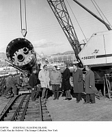 0109754 © Granger - Historical Picture ArchiveCOUSTEAU: FLOATING ISLAND.   French oceanographer Jacques Cousteau (in dark coat) and his engineers watch the lifting of a huge metal tube, to be used as a support in the construction of the 'floating island' marine laboratory in the harbor of Nice, France, 17 December 1962.