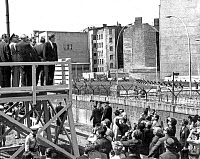 0110339 © Granger - Historical Picture ArchiveKENNEDY IN BERLIN, 1963.   From a platform erected for the occasion, U.S. President John F. Kennedy, visiting West Berlin, 26 July 1963, looks across the Berlin Wall into East Berlin, where buildings have been demolished to clear the ground near the wall.