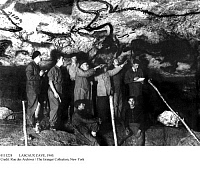 0111224 © Granger - Historical Picture ArchiveLASCAUX CAVE, 1940.   A visit to the cave in Dordogne, France, not long after it was discovered by four teenagers in September 1940. Two of them, Jacques Marsal and Marcel Ravidat, are seated in the foreground. Center, with raised arms, are Count Begoun and Abbé Henri Brueil.