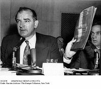 0112398 © Granger - Historical Picture ArchiveJOSEPH McCARTHY (1908-1957).   American politician. Holding up a dossier containing charges against Secretary of the Army Robert T. Stevens during the Army-McCarthy hearings. The Army accused McCarthy and Roy Cohn (right) of seeking special treatment for Pvt. G. David Schine, a chief consultant to the Permanent Subcommittee on Investigations, in 1954.