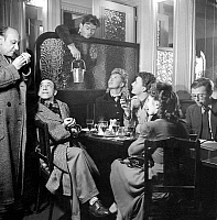 0112461 © Granger - Historical Picture ArchiveSARTRE: CAFÉ SCENE, 1943.   French philosopher and writer Jean-Paul Sartre (far right) at work in the Café de Flore in Saint-Germain-des-Prés, Paris, France, in 1943, while seated next to a group of actors. Left to right: Yves Deniaud, Raymond Bussiere, Maurice Baquet, Marianne Hardy, Roger Pigaut, and Annette Poivre. Photographed by Seeberger Brothers.