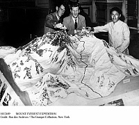 0112489 © Granger - Historical Picture ArchiveMOUNT EVEREST EXPEDITION.   Mountaineer Edmund Hillary (left), Colonel George Hunt (center), and Sherpa guide Tenzing Norgay photographed with a model of Mount Everest in London, England, 7 June 1953, after returning from their successful ascent to the summit of Everest nine days earlier.
