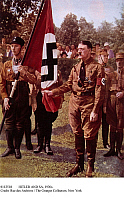 0112518 © Granger - Historical Picture ArchiveHITLER AND SA, 1930s.   Adolf Hitler, with SA troops, holding the bloodied swastika flag from the 'Beer Hall Putsch,' the failed Nazi uprising at Munich, Germany, of 9 November 1923, at a commemoration of the event in the early 1930s.
