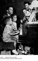 0112643 © Granger - Historical Picture ArchiveFRANK SINATRA (1915-1998).   American singer and actor. At the piano with his children, Nancy and Frank Jr., while wife Nancy Barbato looks on, c1948.