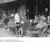 0112757 © Granger - Historical Picture ArchiveWORLD WAR II: PARIS, 1944.   American soldiers and members of WAC (the Women's Army Corps) reading the 'Stars and Stripes' at a sidewalk cafe on Champs-Élysées after the Allied liberation of Paris in August 1944.