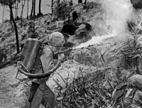 0112915 © Granger - Historical Picture ArchiveWORLD WAR II: IWO JIMA.   An American soldier aims a flame thrower against a cave holding Japanese soldiers during the Battle of Iwo Jima island, February-March 1945.
