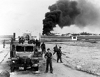 0139218 © Granger - Historical Picture ArchiveEGYPT: SUEZ CRISIS, 1956.   British paratroopers near Port Said, Egypt, with oil tanks shown burning in the distance, at the time of the Suez Crisis, 6 November 1956.