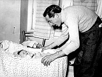 0141516 © Granger - Historical Picture ArchiveFAUSTO COPPI.   Fausto Coppi with baby daughter in cradle, 1947. Full credit: AGIP - Rue des Archives / Granger, NYC -- All Rights Reserved.