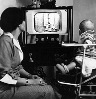 0141596 © Granger - Historical Picture ArchiveFEMME AND SON BEBE DEVANT THE TELE.   A housewife with her baby in a high chair looking television in 1953. Full credit: AGIP - Rue des Archives / Granger, NYC -- All rights reserv