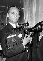 0142221 © Granger - Historical Picture ArchiveFRANCOIS REICHENBACH.   director Francois Reichenbach (1922-1993) in 1966 with his camera at premiere of film Falstaff by OrsonWelles in Maxim's restaurant in Paris. Full credit: AGIP - Rue des Archives / Granger, NYC -- All rights reserved