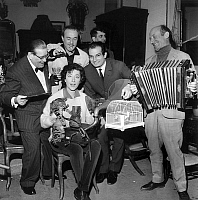 0144550 © Granger - Historical Picture ArchiveHELENE MARTIN.   French singer Helene Martin (with cat) and l-r : Andre Gilles, dress designer Jacques Esterel, dancer Michel Renault, and Olivier Hussenot on april 10, 1962, all gathered in a acfe of the flea market for the new song Saint Ouen's blues. Full credit: AGIP - Rue des Archives / Granger, NYC -- All Rights Reserved.