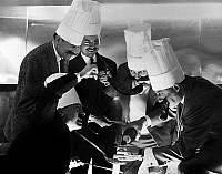 0145692 © Granger - Historical Picture ArchiveJACQUES BOREL AND THE FRERES JACQUES.   For opening of grilled meat restaurant by Jacques Borel, Paris, may 25, 1962 : under look of Jacques Borel, the singers les Freres Jacques cooking. Full credit: AGIP - Rue des Archives / Granger, NYC -- All Rights Reserved.